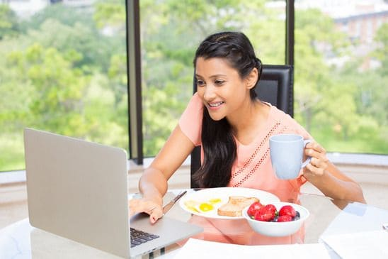 young, attractive businesswoman, kick start day with healthy breakfast, smiling on laptop