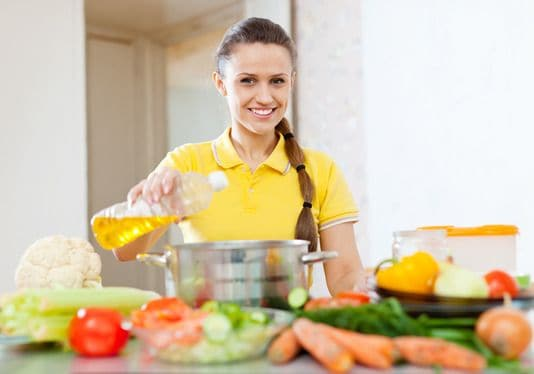 European Woman in Yellow Pouring Oil From Bottle Into The Saucepan