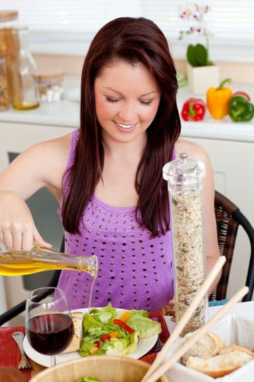 Glowing Young Woman Eating a Salad With Rapeseed oil