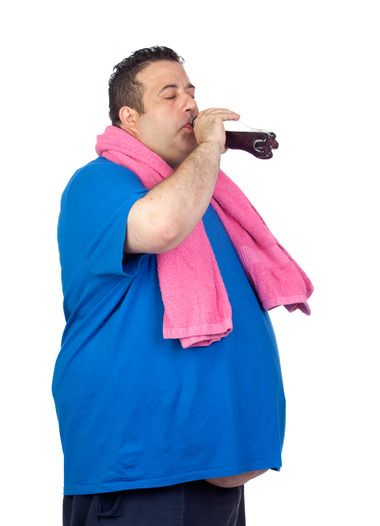 Fat Man In The Gym Drinking Cola Isolated On A White Background